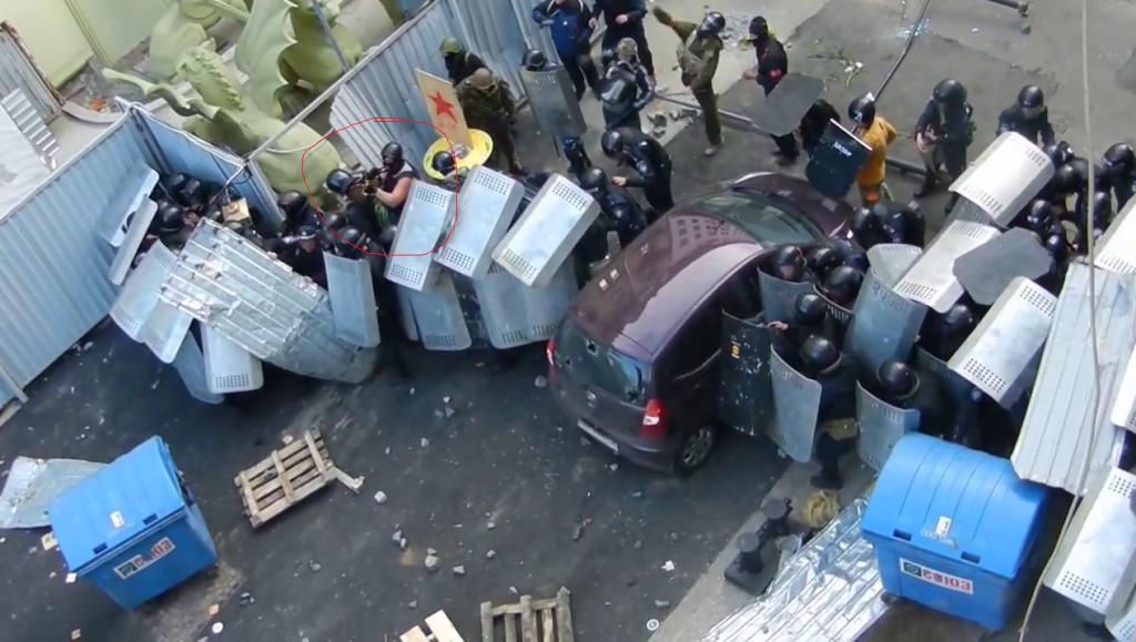 Человек из автомата за спинами милиции стреляет по людям на Дерибасовской.